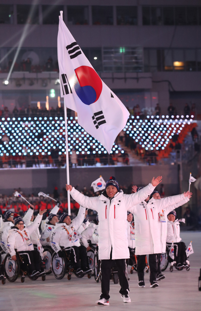 Para Nordic skier Sin Eui-hyun carries the South Korean national flag while the national team enters the Olympic Stadium in Gangwon Province at the opening ceremony for the PyeongChang Paralympics on Friday. (Yonhap)