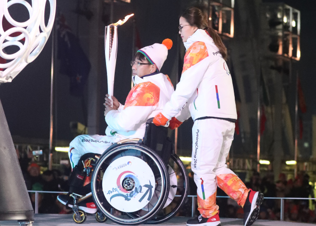 South Korean wheelchair curler Seo Soon-seok(left)andKim Eun-jung, a member of the national women's curling team, were selected tolight the Paralympic cauldron on Friday in Pyeongchang, Gangwon Province. (Yonhap)