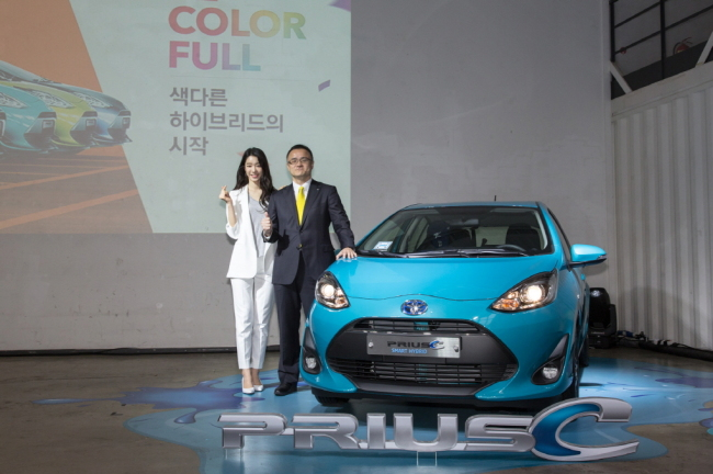 Toyota Korea CEO Nobuyuki Takemura (right) poses next to the Prius C hybrid compact car during the launch event in central Seoul on Wednesday. (Toyota Motor Korea)