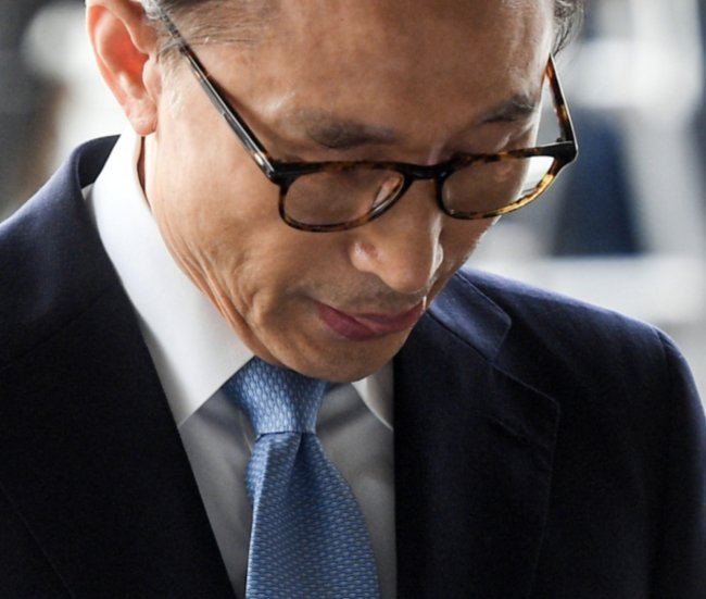 Former President Lee Myung-bak stands in the photo line at the Seoul Central District Prosecutors' Office early in the morning for questioning Wednesday. Yonhap