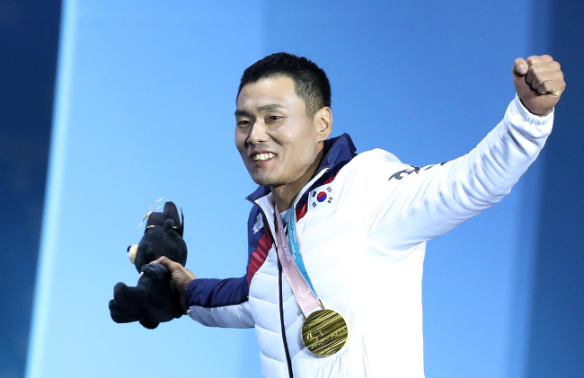 Para Nordic skier Sin Eui-hyun, who won gold in the men`s 7.5km sitting cross-country skiing, raises his arms as he exits the podium at the medal ceremony held at Olympic Plaza in PyeongChang, Gangwon Province on Saturday. (Yonhap)