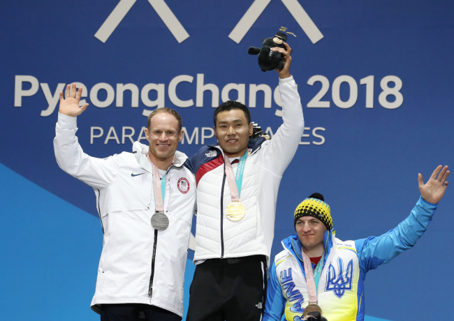 Sin Eui-hyun (center) poses at a medal ceremony held at the Medal Plaza in Gangneung, Gangwon Province, Saturday, after winning the gold medal in the men's 7.5-km sitting cross-country skiing event. Next to him are silver-medalist Daniel Cnossen (left) of the US and Maksym Yarovyi of Ukraine. (Yonhap)