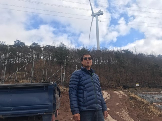 Local farmer Park Chung-lak, who grows apples in the Honggye-ri village in North Gyeongsang Province, speaks in front of his farm. Behind Park lies a 100-meter-high wind turbine that was installed as part of Korea's renewable energy policies. Bak Se-hwan/The Korea Herald