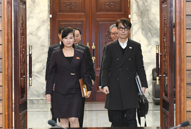 Hyun Song-wol (left), leader of North Korea all-female Moranbong Club and Yun Sang (right), South Korean singer-songwriter enter the Tongilgak administrative building on the northern side of the Demilitarized Zone on Tuesday for working-level talks. (Ministry of Unification)