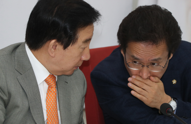 The Liberty Korea Party's chief policymaker Rep. Ham Jin-kyu (right) whispers to party Floor Leader Rep. Kim Sung-tae at an emergency party meeting held at the National Assembly on Sunday. (Yonhap)