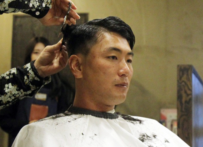 In this photo provided by the SK Wyverns baseball club, Kim Kwang-hyun, the team`s starting pitcher, gets a haircut on March 25, 2018, in Incheon, 40 kilometers west of Seoul. Kim will donate his hair to help make wigs for children who`ve lost their hair following cancer treatment. (Yonhap)