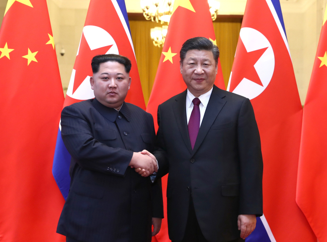 North Korean leader Kim Jong-un, left, shakes hands with Chinese President Xi Jinping on March 28. (Yonhap)