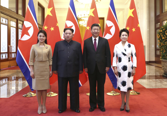 Chinese President Xi Jinping, second from right, and his wife Peng Liyuan, right, and North Korean leader Kim Jong-un, second from left, and his wife Ri Sol-ju , left, pose for a photo at the Great Hall of the People in Beijing. (AP-Yonhap)
