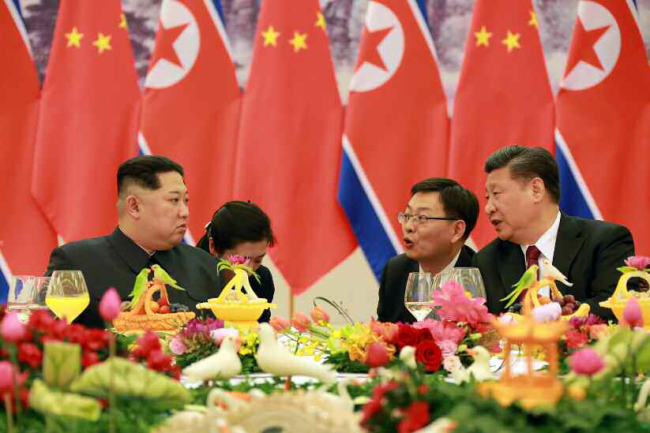 North Korean leader Kim Jong-un, left, is seen talking with Chinese President Xi Jinping on March 28. (Yonhap)