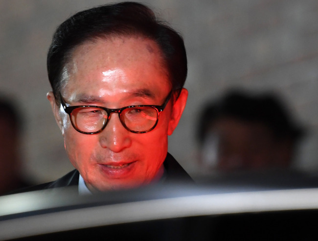 Former President Lee Myung-bak boards a vehicle as he was taken into custody on Friday. (Yonhap)