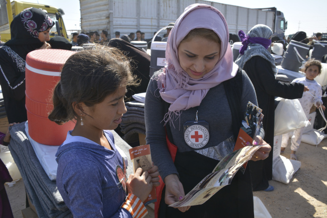 An ICRC worker distributes relief items to an internally displaced person at the Amiryat Al-Someed camp in Anbar province, Iraq. (ICRC)