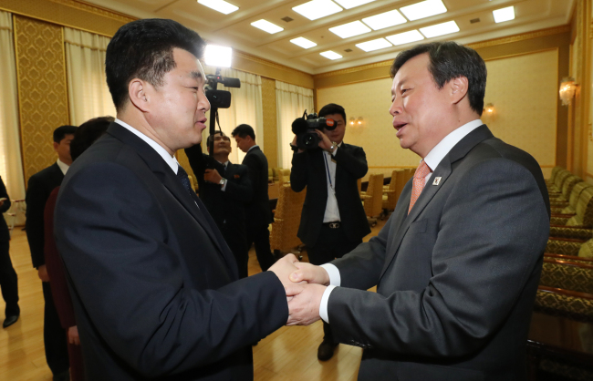 South Korean Sports Minister Do Jong-whan (right) and his North Korean counterpart, Kim Il-guk, shake hands before their meeting at the Mansudae Assembly Hall in Pyongyang on Monday. (Yonhap)