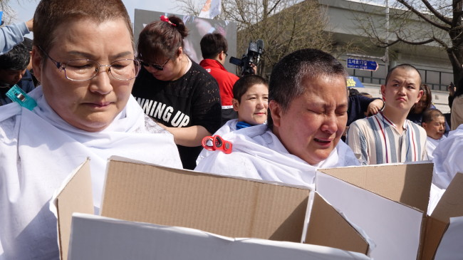 Park Sun-im and Ahn Yoon-ji from Geoje Island shave their heads, demanding state support for those with developmental disorders in front of Hyoja community service center, some 200 meters away from the presidential office, in Seoul on Monday. (Lim Jeong-yeo/The Korea Herald)