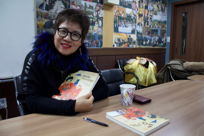 "Park Kyung-hee poses with the English version of her book ""Potato Porridge."" (Sylvia Lee/The Korea Herald)"