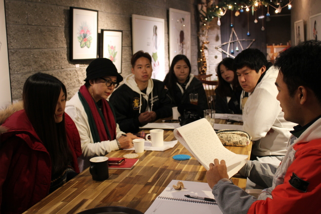 Students discuss story ideas with their teacher, Park Kyung-hee, at a Mulmangcho Open School writing class. (Mulmangcho)