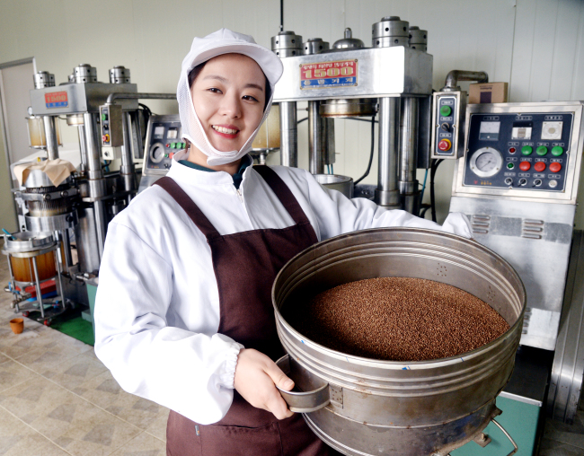 Song Ju-hee holds a pot of roasted sesame seeds at her sesame oil factory in Hwacheon, Gangwon Province. (Park Hyun-koo/The Korea Herald)