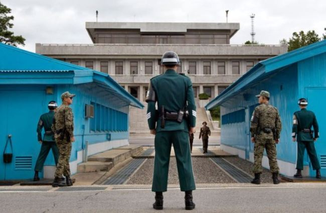 South Korean soldiers look toward the North Korean side as a North Korean solder approaches the UN truce village building that sits on the border of the Demilitarized Zone. (AP)