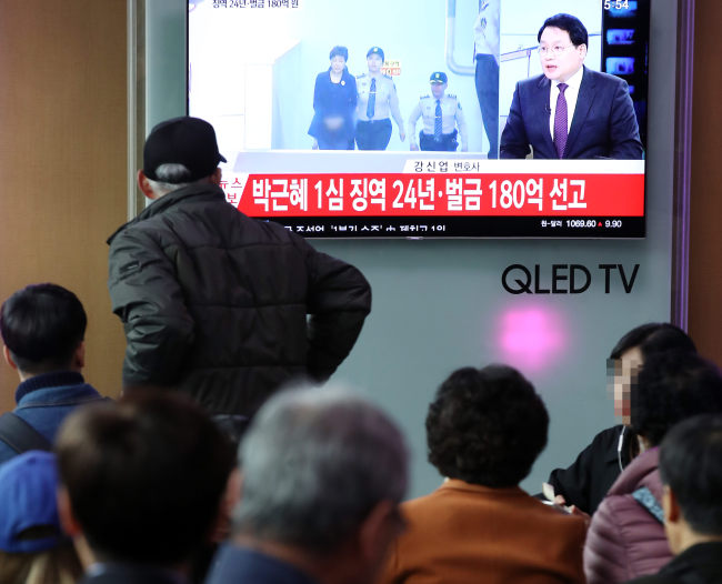 Passersby watch as Park Geun-hye's sentencing is broadcast live on a television at Seoul Station, Friday. (Yonhap)
