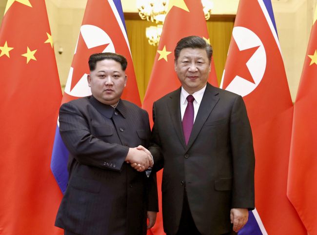 In this file photo provided Wednesday, March 28, 2018, by China's Xinhua News Agency, North Korean leader Kim Jong Un, left, and Chinese President Xi Jinping shake hands in Beijing. (Yonhap-AP-Xinhua)