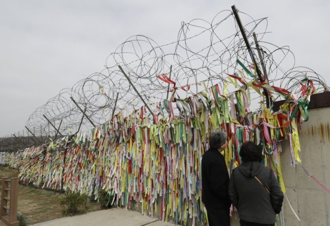 Visitors look at the ribbons carrying messages wishing the reunification and peace of the two Koreas at the Imjingak Pavilion in Paju, South Korea, Saturday, April 7. (AP)