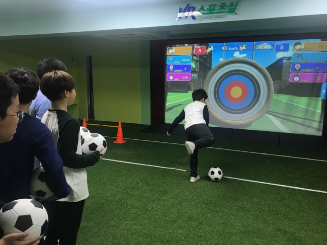 Students practice kicking a ball at virtual objects on the screen in Seoul Banghak Elementary School's indoor sports facility. Bak Se-hwan/The Korea Herald