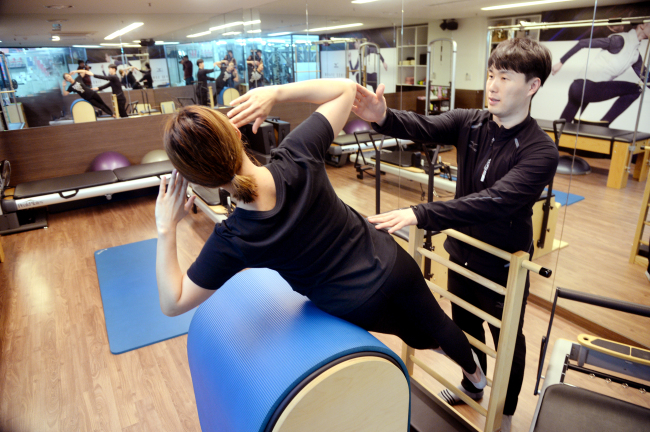 Pilates instructor Lee Su-yeol helps a student to accurately position her body on a board. (Park Hyun-koo/The Korea Herald)