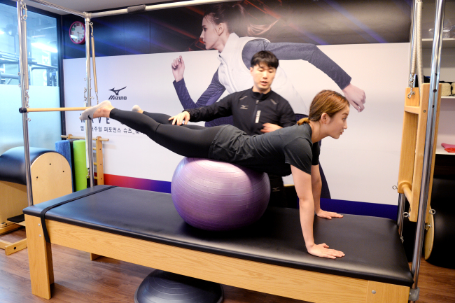 Lee Su-yeol instructs a student on how to balance her body on a ball. The exercise improves core muscle strength and balance. (Park Hyun-koo/The Korea Herald)