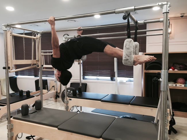 Sports creator Leo Jung performs an advanced stretch on the Pilates Cadillac. (Photo courtesy of Leo Jung)