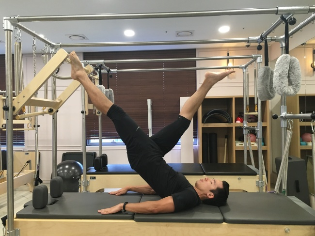 Leo Jung performs an advanced inverted hanging scissors on the Pilates Cadillac. (Photo courtesy of Leo Jung)