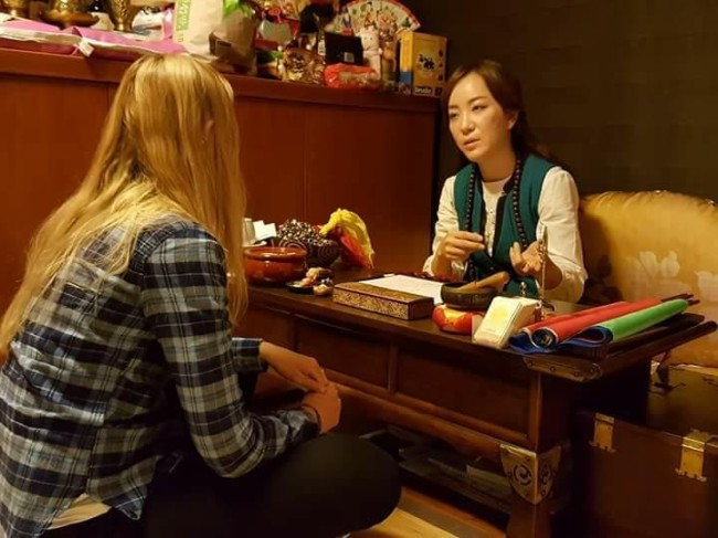 Korean mudang Pang Eun-mi offers consultation to her client at her house in Ilsan. (Photo courtesy of Pang Eun-mi)