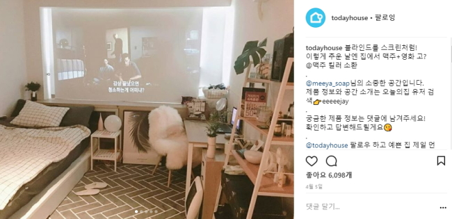 Instagram user @meeya_soap projects a movie onto window blinds inside a studio apartment decorated with plants and wooden furniture. (Instagram)