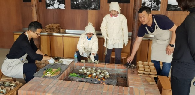 A picture of haenyos and Hyundai Card's chef cooking seafood at the fishery center (Photo by Shim Woo-hyun / The Korea Herald)