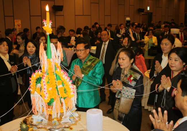Lao Ambassador to Korea Khamsouay Keodalavong (in green shirt) prays in front of a pah kwan as part of the traditional Lao ceremony Baci during a reception in Seoul on Friday (Lao Embassy)