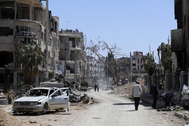 Syrians walk through destruction in the town of Douma, the site of a suspected chemical weapons attack, near Damascus, Syria, Monday, April 16, 2018. (AP-Yonhap)