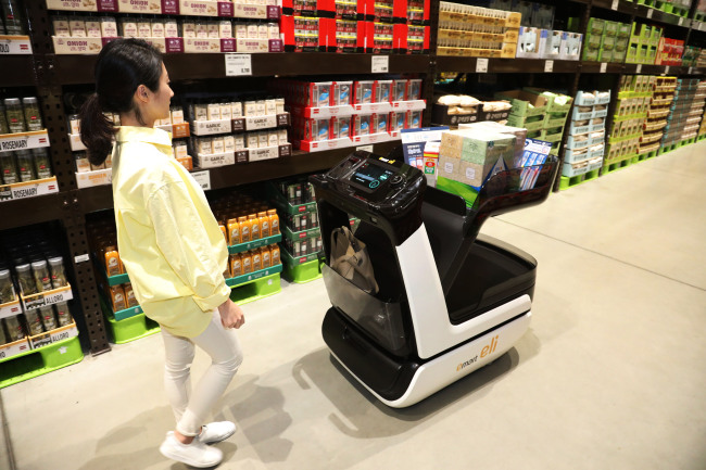 A model tries out E-mart's autonomous shopping cart Eli at E-mart Traders in Hanam, Gyeonggi Province, Tuesday. (E-mart)
