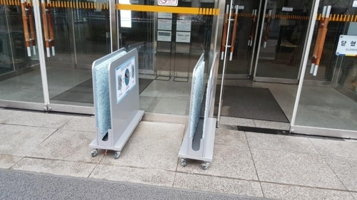 A pair of umbrella dryers are placed at the entrance of a building. (Photo courtesy of Seoul Metropolitan Government)
