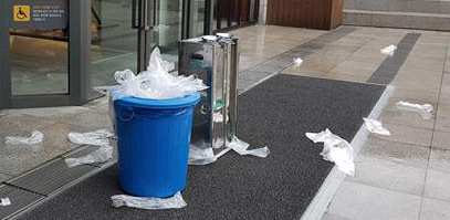 Used plastic umbrella sleeves are littered on the ground near the entrance of a building. (Yonhap)