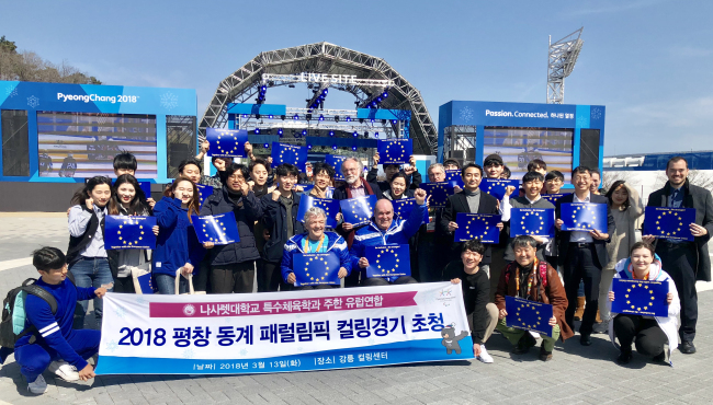 ropean Union Ambassador to Korea Michael Reiterer (center) poses with Korean university students at a 2018 PyeongChang Paralympic curling match on Mar. 13. (European Union Delegation in Korea)