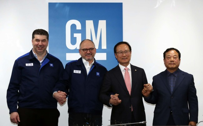 GM Korea CEO Kaher Kazem (first right) and GM Executive Vice President Barry Engle (second right) pose with officials after reaching tenative agreementjust an hourbeforethedeadlineatthe carmaker's Bupyeong factory on Monday afternoon. (Yonhap)