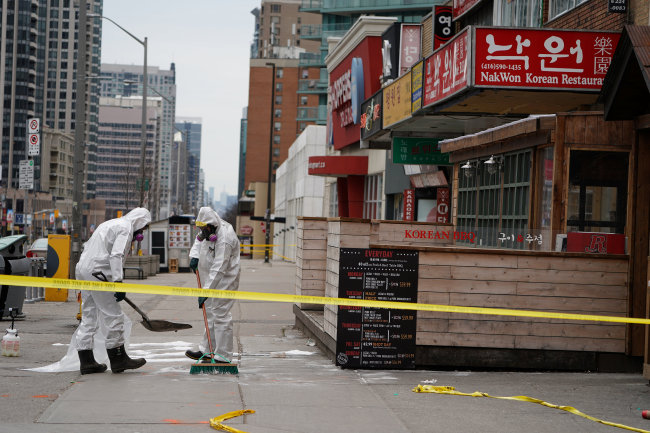 Workers clean up blood stains in Yonge and Finch area in Toronto, Canada, known as one of the Koreatowns there, following a van that attacked multiple people. (Yonhap)