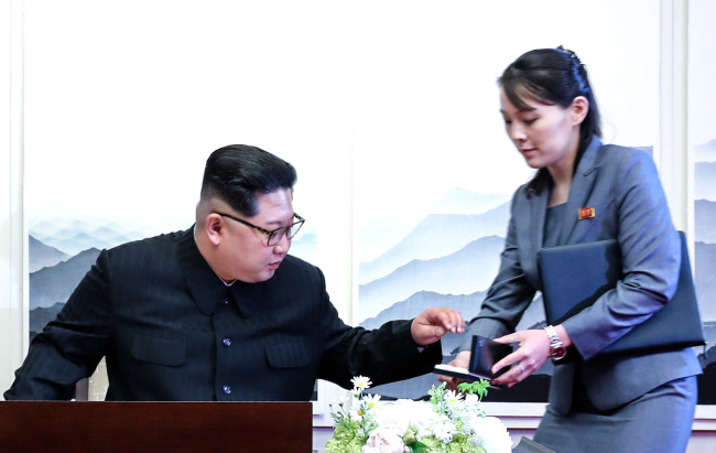 North Korean leader Kim Jong-un receives a Montblanc fountain pen from his sister Kim Yo-jong as he prepares to write a message in the visitors' book as he entered the Peace House on Friday. (Yonhap)