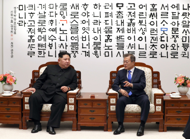 North Korea's leader Kim Jong-un (left) and South Korea's President Moon Jae-in converse during the inter-Korean summit at the truce village of Panmunjeom on Friday. (Yonhap)