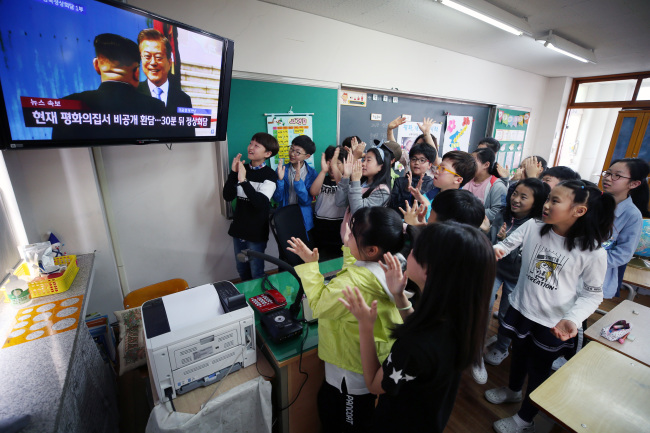 Students at an elementary school in Gwangju, Jeolla Province, cheer in joy as they watch North Korean leader Kim Jong-un shake hands wiht his South Korean counterpart Moon Jae-in in the first summit for the two Koreas in over a decade. (Yonhap)