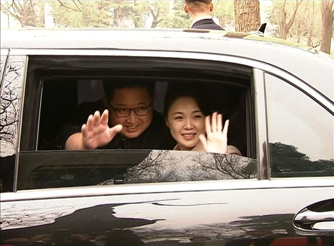 North Korean leader Kim Jong-un and his wife Ri Sol-ju wave from a car as they bid farewell to Chinese counterpart Xi Jinping and his wife Peng Liyuan in Beijing on March 27. (AP-Yonhap)
