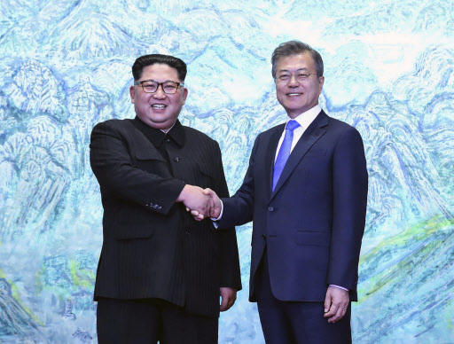 North Korean leader Kim Jong Un, left, shakes with South Korean President Moon Jae-in inside the Peace House at the border village of Panmunjom in Demilitarized Zone Friday, April 27, 2018. Their discussions will be expected to focus on whether the North can be persuaded to give up its nuclear bombs. (Korea Summit Press Pool via AP) (Yonhap)