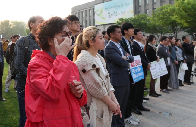 Seoul citizens tear up as they watch the leaders of two Koreas announce the Panmunjeom Declaration on Friday in central Seoul. (Yonhap)