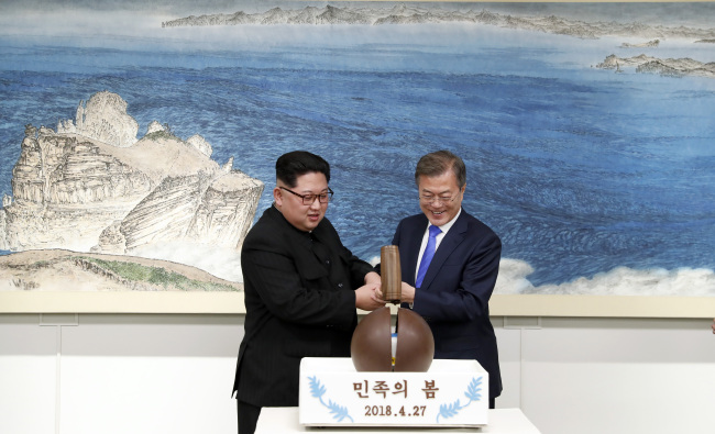 North Korean leader Kim Jong-un (left) and South Korean President Moon Jae-in (right) break a chocolate dome together while dessert is being served during a dinner event following the inter-Korean summit in Panmumjeom on Friday (Yonhap).