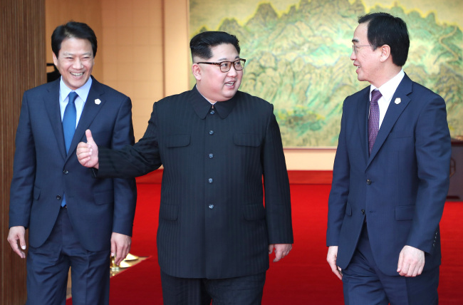 North Korean leader Kim Jong-un (center) talks with South Korean Unification Minister Cho Myoung-gyon (right) as he comes out of talks with his South Korean counterpart Moon Jae-in at the Peace House of the truce village of Panmunjom on Friday. Moon`s chief of staff, Im Jong-seok, is on the left. (Yonhap)