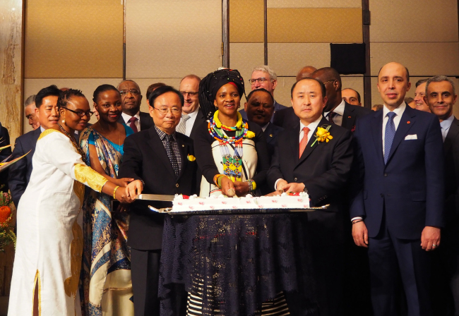 South African Ambassador to Korea Nozuko Gloria Bam (center in traditional South African dress) takes part in a cake-cutting ceremony at a Freedom Day celebration in Seoul on Thursday in the company of ambassadors and diplomats. (Joel Lee/The Korea Herald)