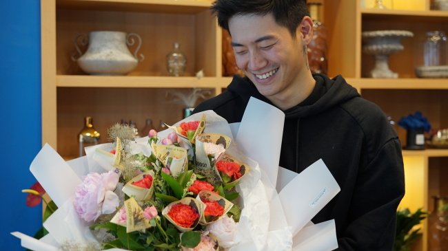 Florist Jung Jun-ho poses for a picture with a money-wrapped flower bouquet at Peony Pepe flower shop, located in Cheongdam-dong, southern Seoul on May 1. (Park Ju-young/The Korea Herald)